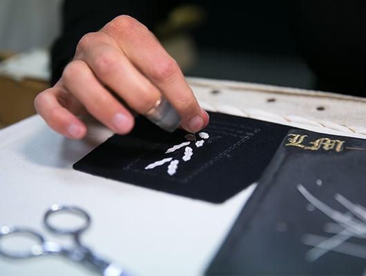 Zoom sur le travail d'une broderie faite main pour illustrer l'expertise de BBA.