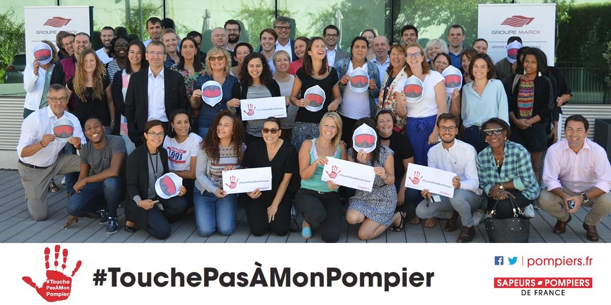 Photographie de collaborateurs réunis pour l'opération #TouchePasAMonPompier.