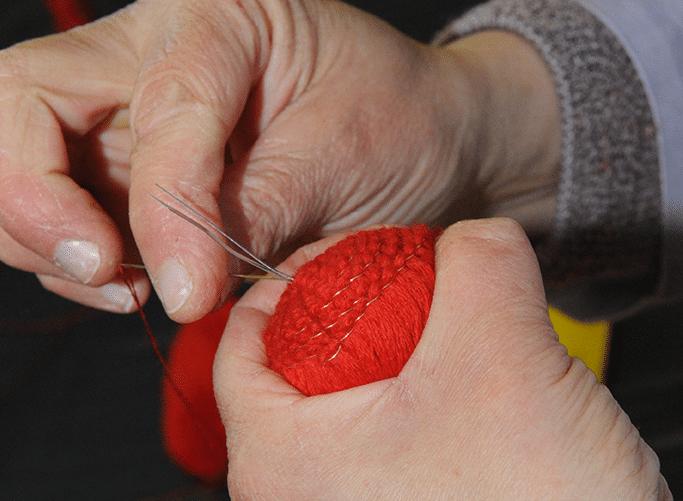 Zoom sur une étape de confection d'un pompon rouge des marins.